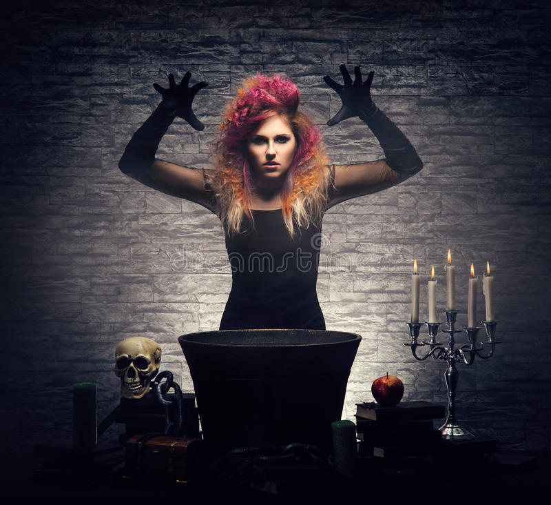 Młoda czarownica robi guślarstwu w Hallowen dungeon zdjęcia royalty free