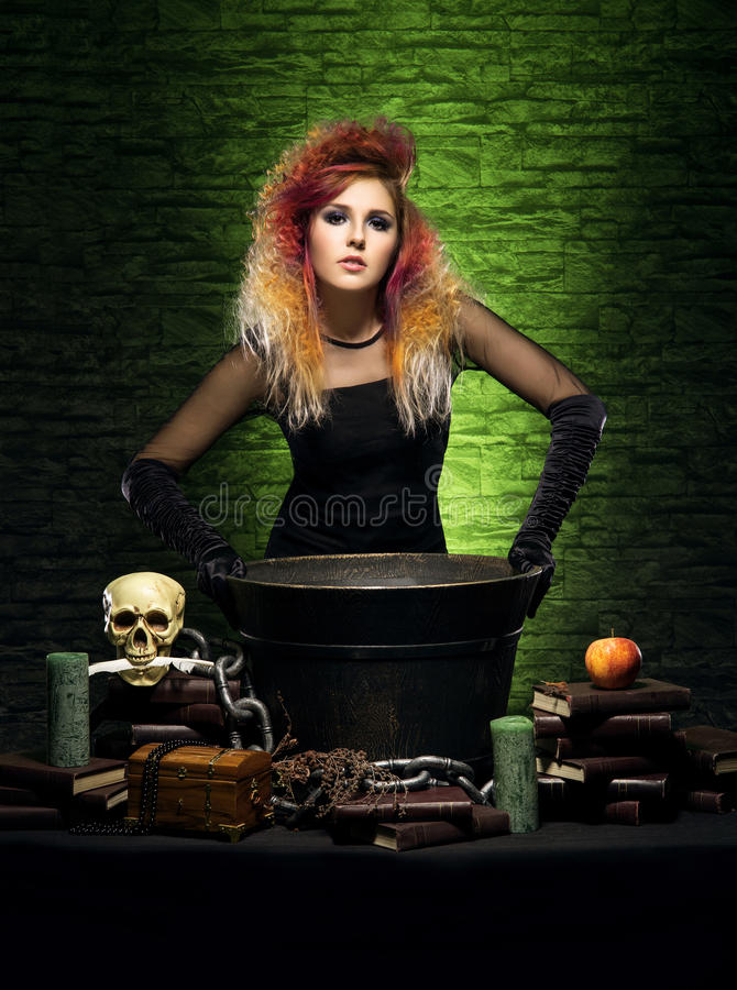 Młoda czarownica robi guślarstwu w Hallowen dungeon fotografia royalty free