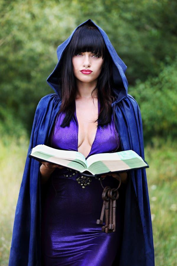 Młoda czarownica z książką zdjęcie stock