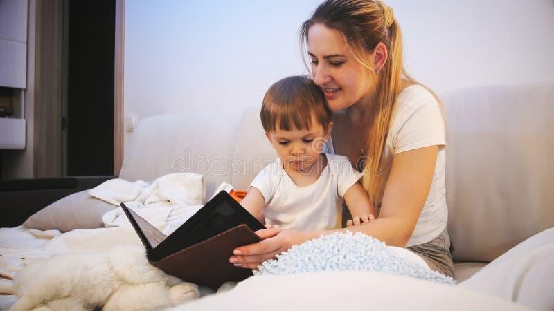 Młoda czułości matka czyta pora snu opowieść jej berbeć chłopiec w piżamach zdjęcie stock