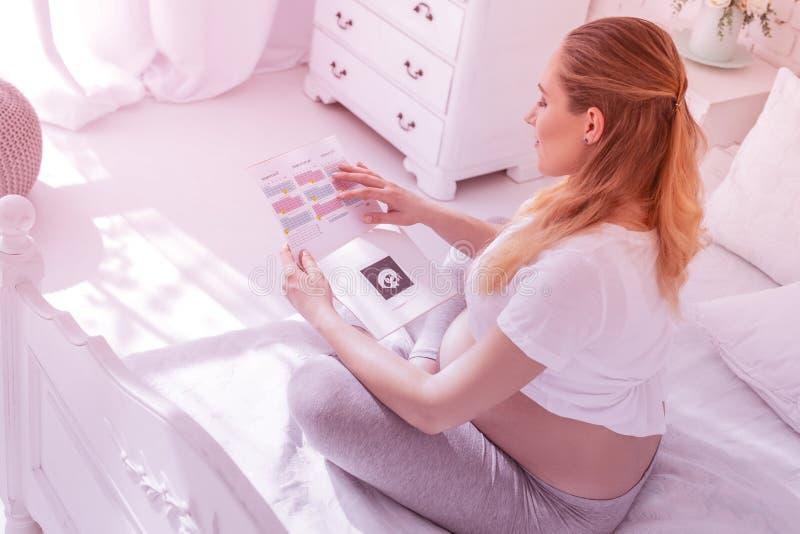 Młoda długowłosa kobieta w ciąży patrzeje kalendarz w białej koszulce obrazy stock