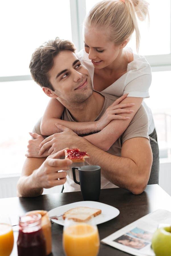 Młoda dama ściska jej mężczyzna podczas gdy śniadanie obraz stock