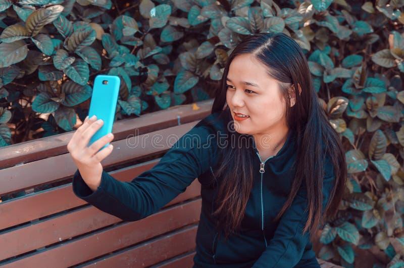 Młoda dama bierze selfie na ławce używać jej mądrze telefon zdjęcia stock