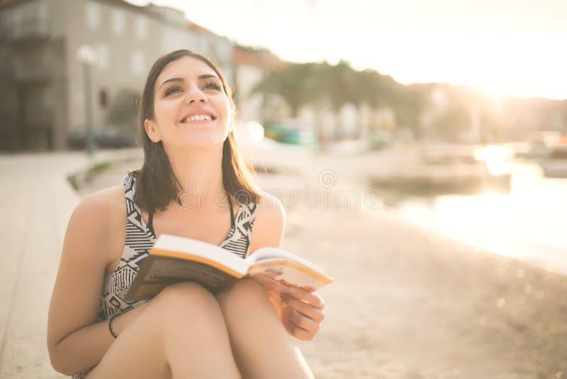 Młoda dama czyta książkę na plaży przy zmierzchem Wakacje letni i wakacje obrazy stock