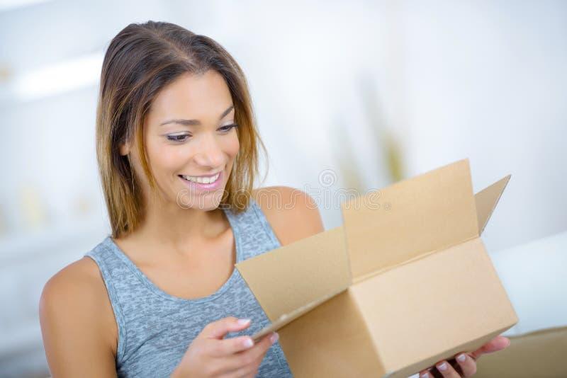 Młoda dama patrzeje w otwartego karton zdjęcie stock