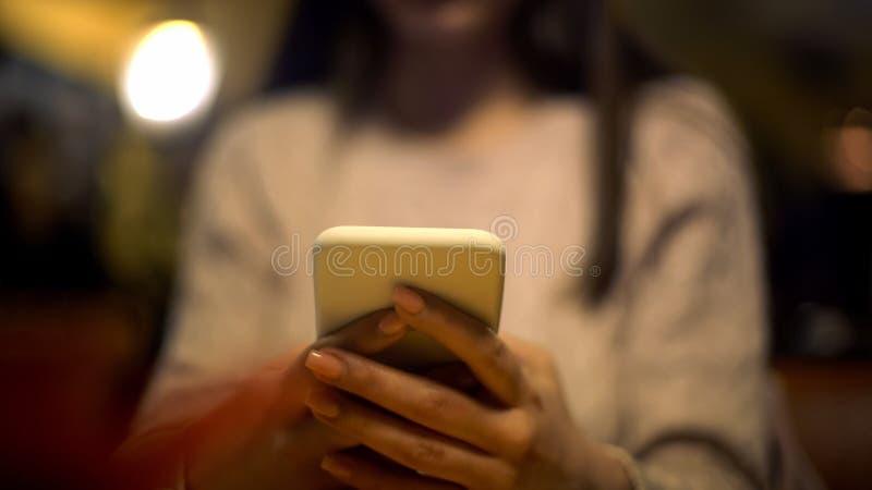 Młoda dama pisać na maszynie na smartphone sprawdza pocztę, online hotelowa rezerwacja, zastosowanie obrazy stock