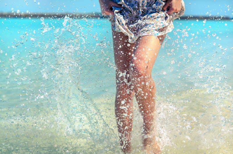 Młoda dama robi wod pluśnięciom z jej nogami Wakacje i lata nastrój zdjęcie stock