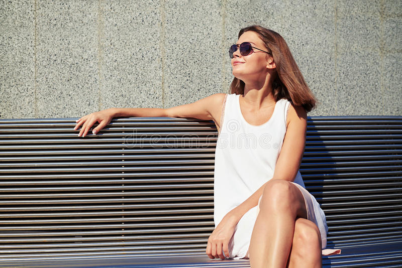 Młoda dama siedzi na ławce i cieszy się lato su w okularach przeciwsłonecznych obraz royalty free
