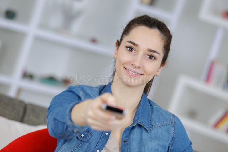 Młoda dama używa pilota do tv obrazy stock