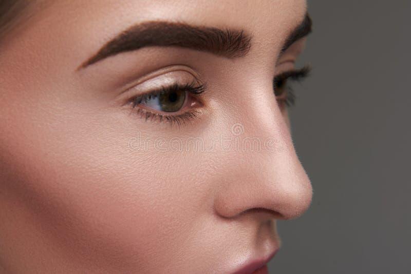 Młoda dama z czystą skórą i ufnym spojrzeniem pozuje na szarym tle obrazy royalty free