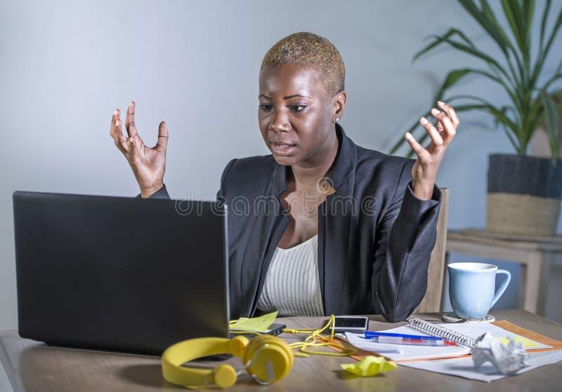 Młoda desperackiego i zaakcentowanego amerykanina afrykańskiego pochodzenia biznesowa kobieta pracuje przy laptopu biurkiem przy  obrazy royalty free