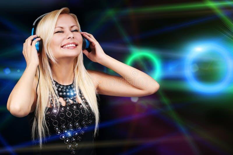 Młoda DJ kobieta z hełmofonami szczęśliwa blondynki dziewczyna zdjęcia stock