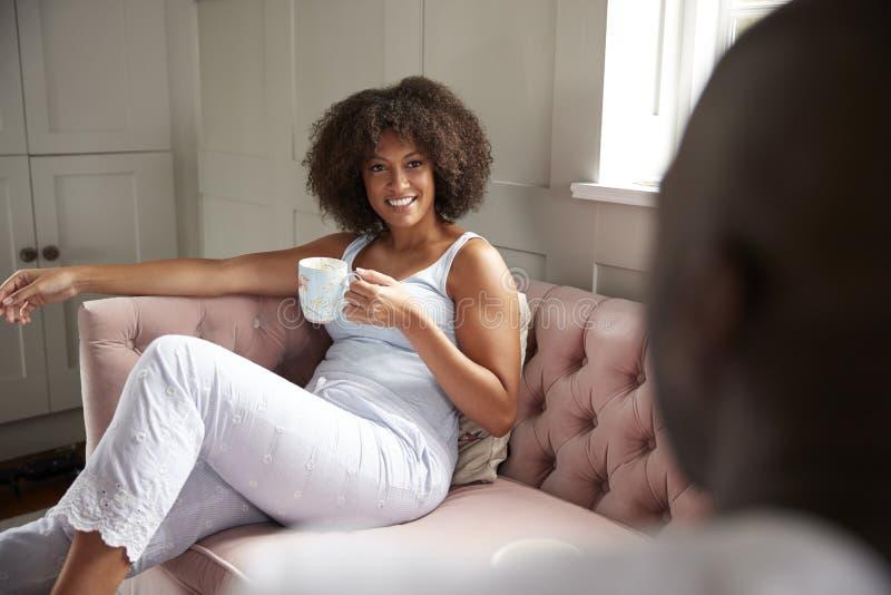 Młoda dorosła czarna para siedzi pić kawowy patrzejący each inny w ranku nad naramiennym widokiem, zakończenie w górę obrazy stock