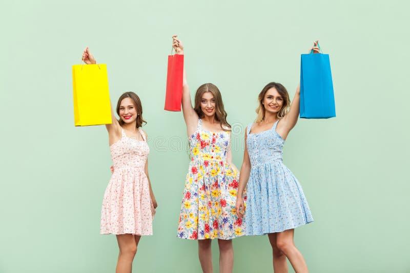 Młoda dorosła dziewczyna w sukni, pokazuje ona torby po robić zakupy Ręki up i trzymający jej kolorowe torby zdjęcie royalty free