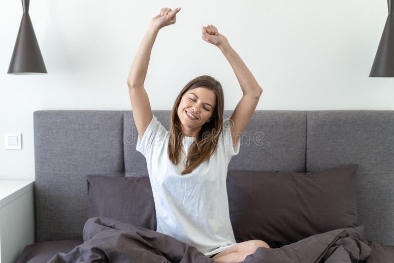 Młoda dorosła kobieta awaiking na łóżku w ranku zdjęcia stock