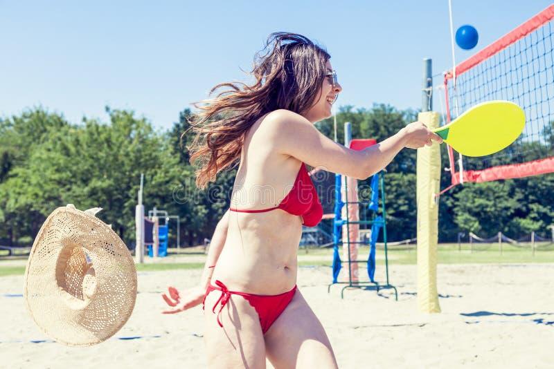 Młoda dorosła kobieta bawić się tenisa na plaży obrazy stock