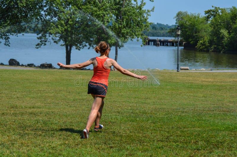 Młoda dorosła kobieta biega przez kropideł w parku w lecie Pojęcie dla beztroskiego utrzymania zdjęcia stock