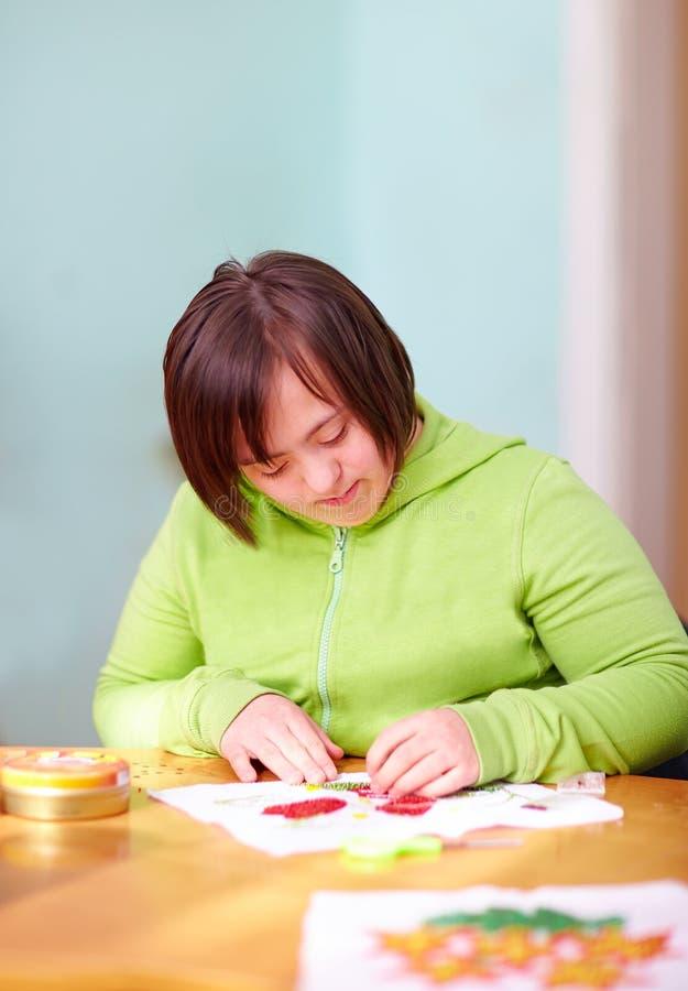 Młoda dorosła kobieta z kalectwem angażował w craftsmanship w centrum rehabilitacji zdjęcia royalty free