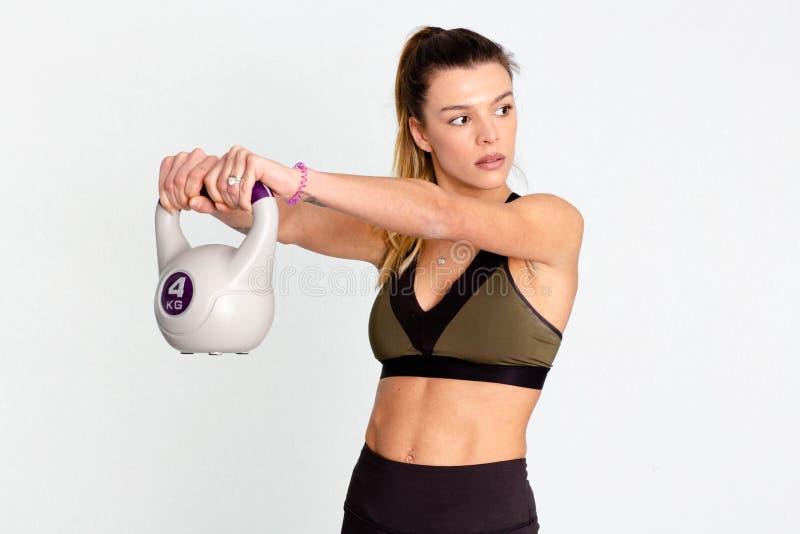 Młoda dorosła sprawności fizycznej kobieta robi huśtawkowemu ćwiczeniu z kettlebell jako część sprawność fizyczna trening - wizer obrazy royalty free