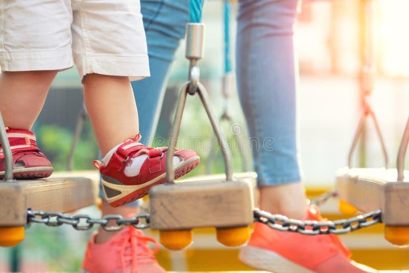 Młoda dorosły matka z małym ślicznym berbecia dzieckiem ma zabawę cieszy się czas wolny gry przy plenerowym boiskiem na jaskrawym zdjęcia stock