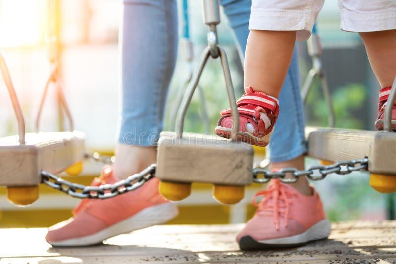 Młoda dorosły matka z małym ślicznym berbecia dzieckiem ma zabawę cieszy się czas wolny gry przy plenerowym boiskiem na jaskrawym fotografia stock