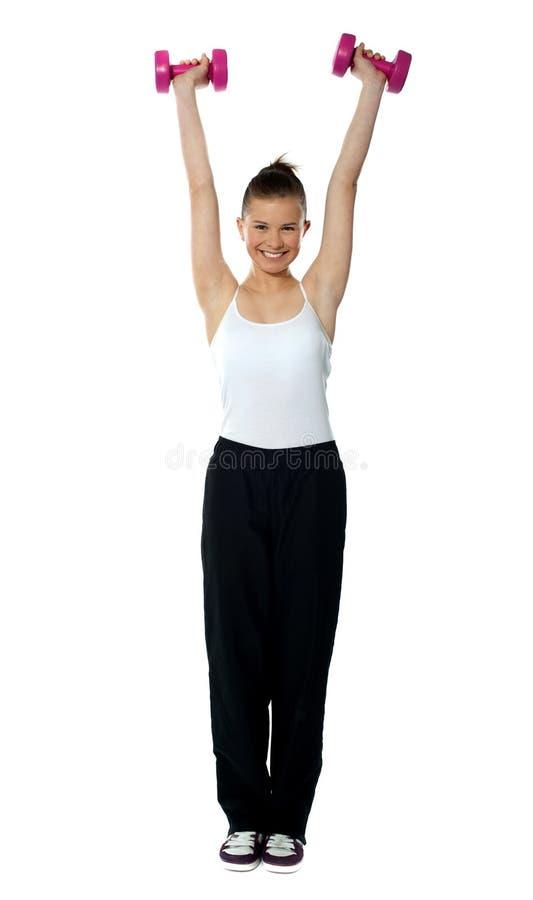 Młoda dziewczyna ćwiczy z dumbbells zdjęcia stock