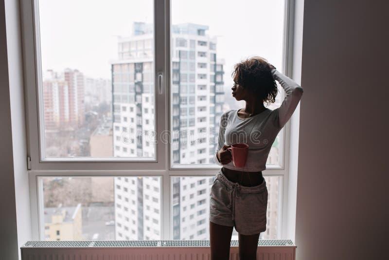 Młoda dziewczyna, afrykański nastoletni patrzeć przez dużego okno z wieżowami i trzymać kawę, herbaciany kubek w pokoju w domu obraz royalty free
