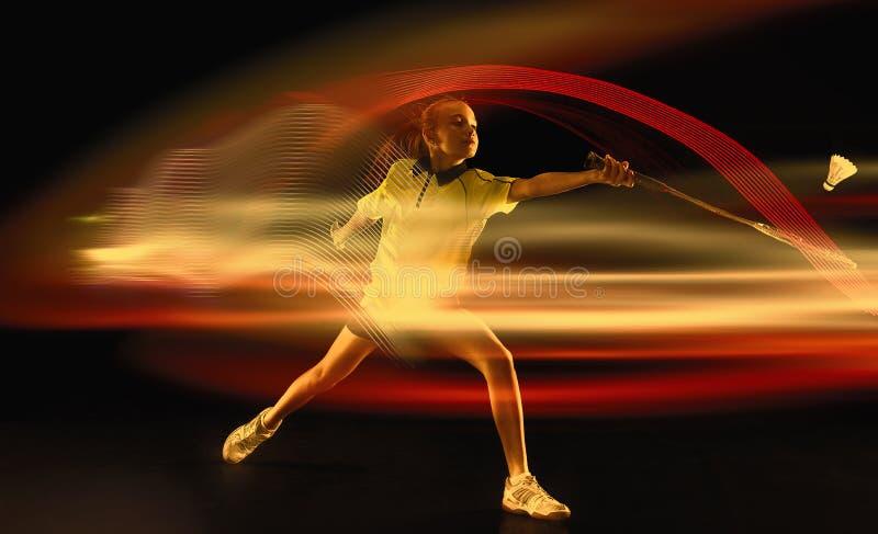 Młoda dziewczyna bawić się badminton nad ciemnym tłem fotografia stock