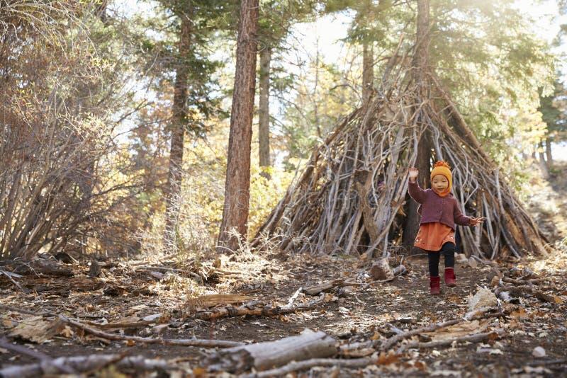 Młoda dziewczyna bawić się outside budę robić gałąź w lesie obraz stock