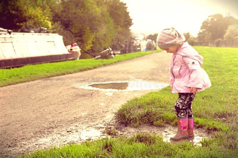 Młoda dziewczyna bawić się w błotnistej kałuży na kanałowej ścieżce obraz royalty free