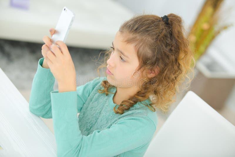 Młoda dziewczyna bawić się z telefonem komórkowym fotografia stock