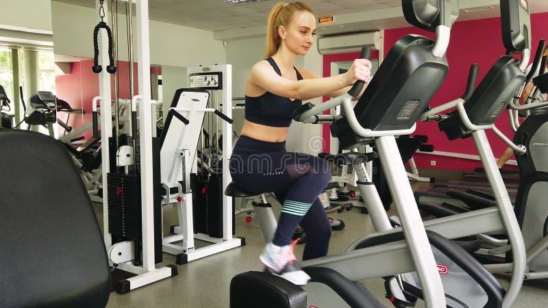 Młoda dziewczyna bieg na ćwiczenie rowerze w sporta gym obrazy royalty free