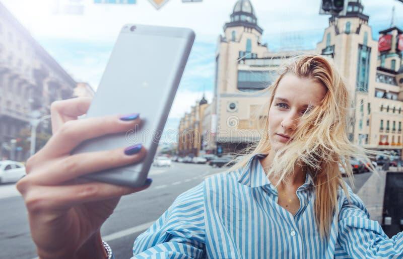 Młoda dziewczyna bierze selfie na smartphone, dzień, plenerowy w mieście zdjęcie stock