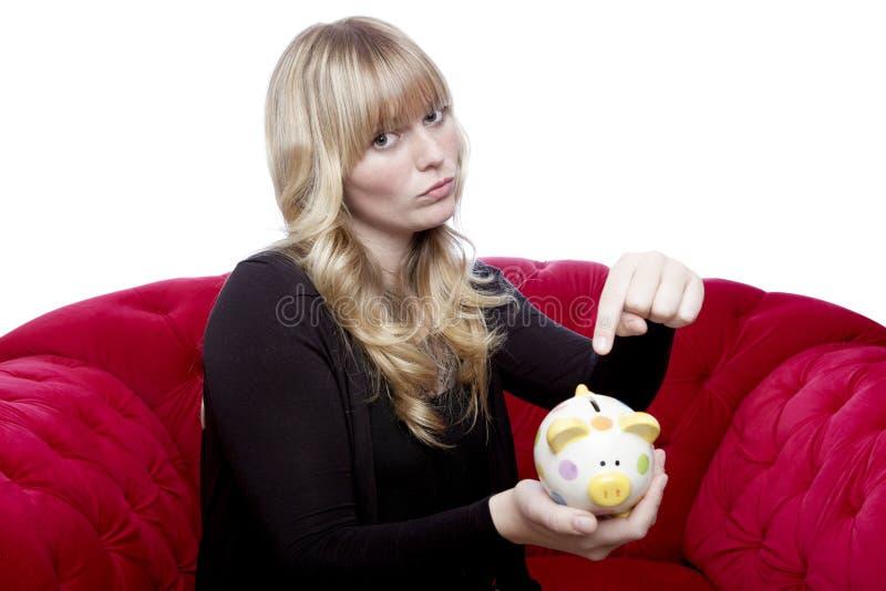 Młoda dziewczyna chcieć pieniądze w jej piggybank fotografia royalty free