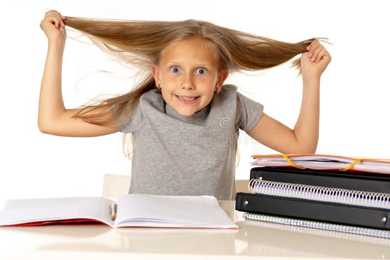 Młoda dziewczyna ciągnie jej włosy w stresie nad pracującym edukaci pojęciem i fotografia royalty free