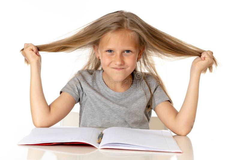 Młoda dziewczyna ciągnie jej włosy w stresie nad pracującym edukaci pojęciem i fotografia stock