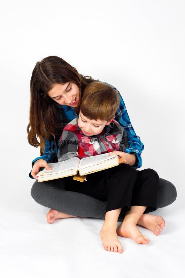 Młoda Dziewczyna Czyta biblię Jej młodszy brat obraz royalty free