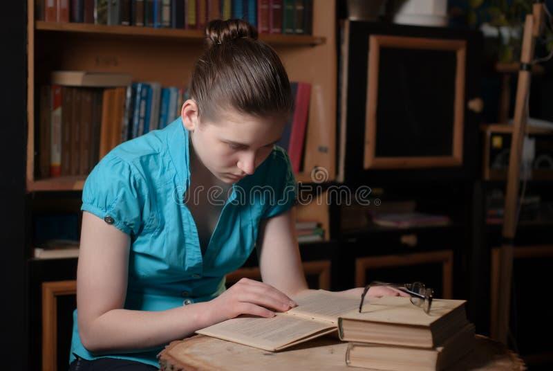 Młoda dziewczyna czyta książkę w szkłach fotografia royalty free
