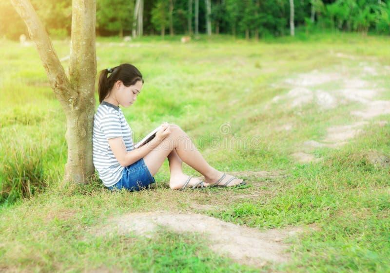 Młoda dziewczyna czyta książkę w zielonej łąkowej contryside naturze obraz royalty free
