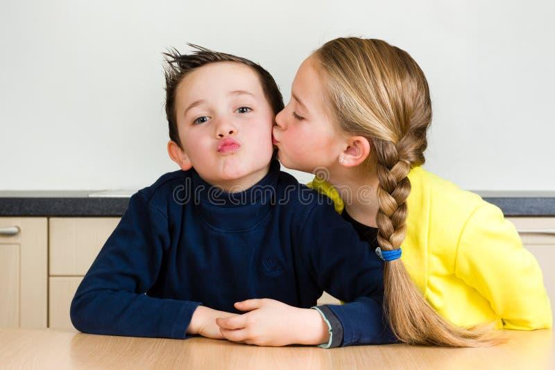 Młoda dziewczyna daje jej bratu buziakowi fotografia stock