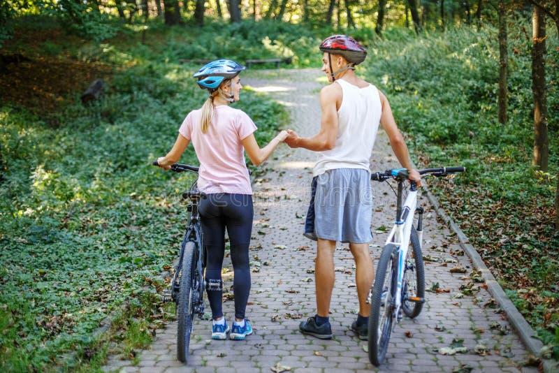 Młoda dziewczyna i chłopiec z bicyklami w parku Pojęcie cyc obrazy royalty free