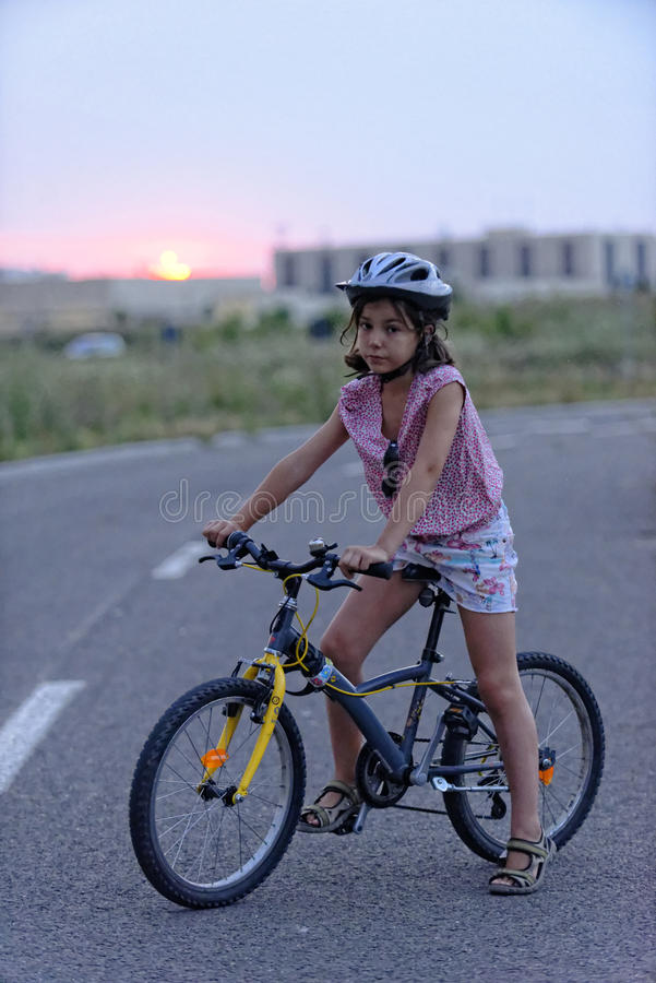Młoda dziewczyna i jej bicykl w drodze zdjęcie royalty free