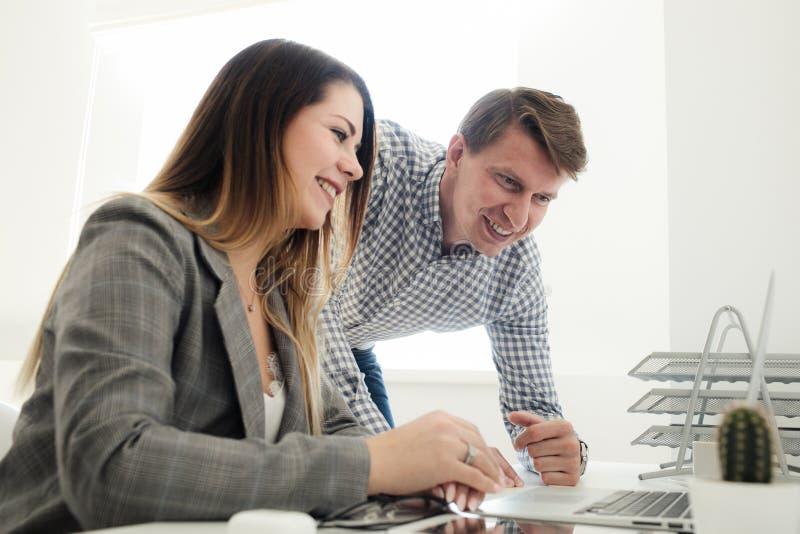 Młoda dziewczyna i mężczyzna pracuje w biurze przy stołem obraz royalty free