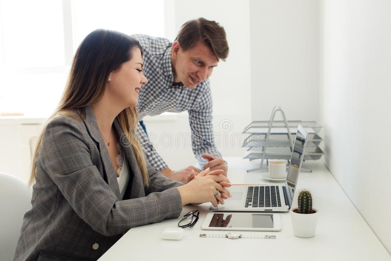 Młoda dziewczyna i mężczyzna pracuje w biurze przy stołem obraz stock