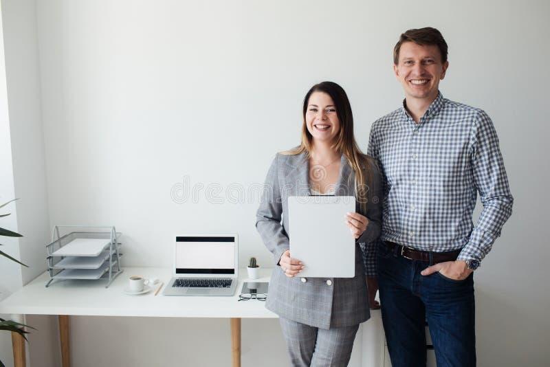 Młoda dziewczyna i mężczyzna pracuje w biurze przy stołem zdjęcia stock