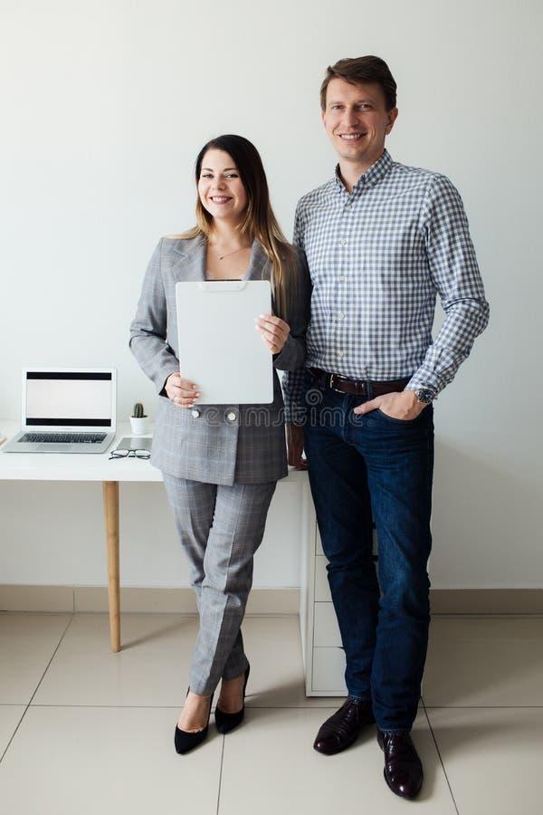Młoda dziewczyna i mężczyzna pracuje w biurze przy stołem fotografia stock