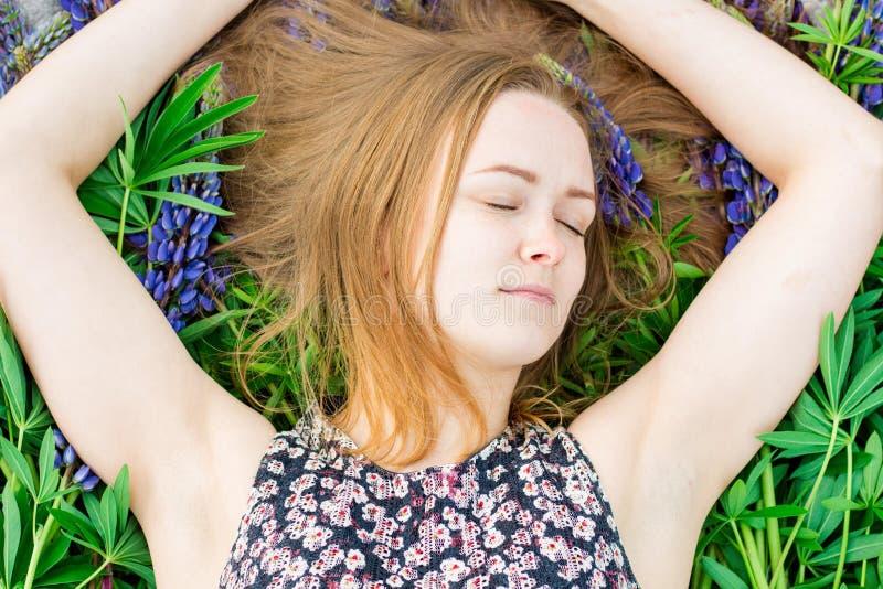 Młoda dziewczyna i piękny kłamamy na bedspread kwiaty fotografia stock