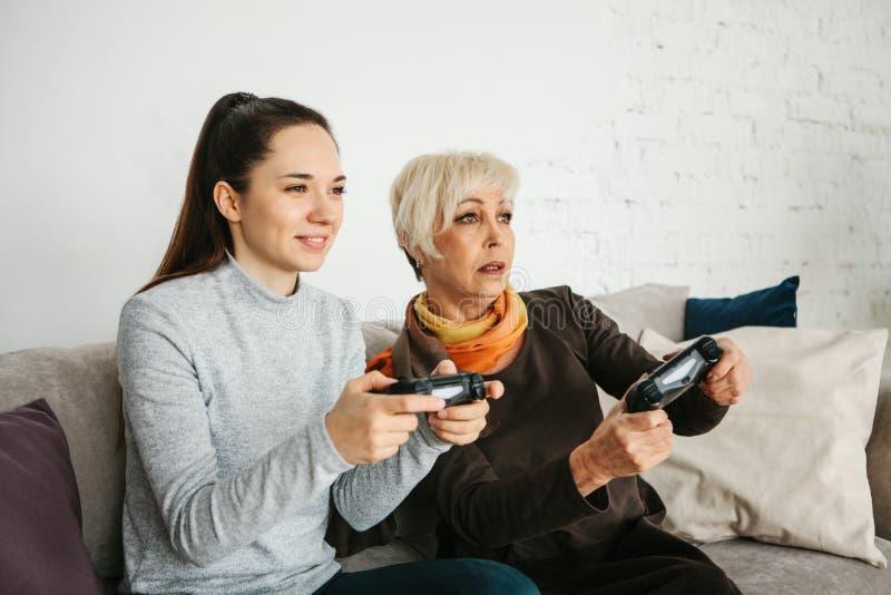 Młoda dziewczyna i starsza kobieta bawić się wpólnie w wideo grą Łączna rozrywka Życie Rodzinne Komunikacja zdjęcia royalty free