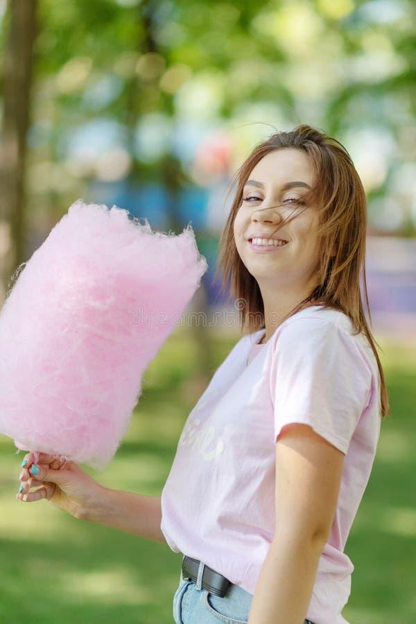 Młoda dziewczyna je bawełnianego cukierek w parku fotografia royalty free