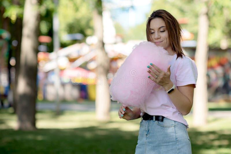 Młoda dziewczyna je bawełnianego cukierek w parku fotografia stock